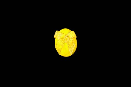 Yellow easter egg with shiny bow on black background. Festive concept, minimalism. Close-up, copy space