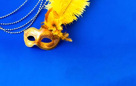 Carnival mask on blue background with silver beads. Festivals or Mardi Gras concept. Copy space