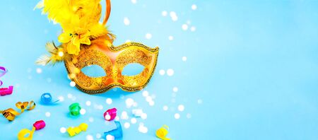 Golden Carnival mask on blue background with with colored confetti. Mardi gras festive concept. Copy space, close-up Stock Photo