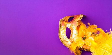 Golden Carnival mask on purple background. Mardi Gras concept. Copy space, close-up