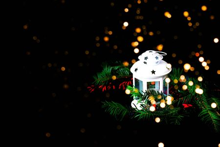 Christmas white lantern on black background with sparkles. Blurred effect. Copy space