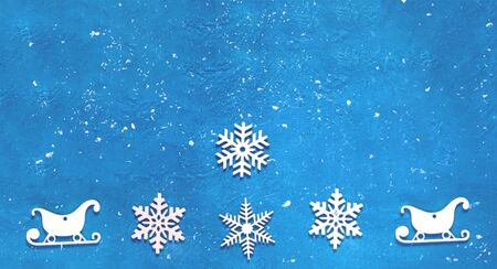 Decorative wooden Christmas snowflakes and sleighs on blue background. Festive New Year card in trendy color