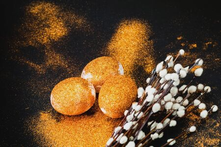 Easter eggs decorated with golden spangles on black background. Festive concept, minimalism. Close-up Stock Photo