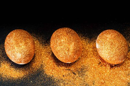 Easter eggs decorated with golden spangles on black background. Festive concept, minimalism. Close-up, copy space Stock Photo
