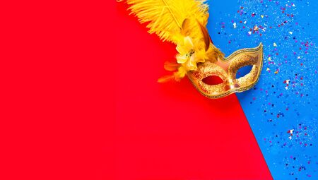 Golden Carnival mask on geometric colored background with sparkles and silver beads. Mardi Gras concept. Copy space