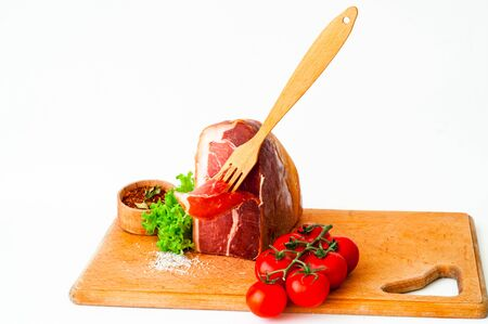 Authentic Italian Prosciutto Dry-Cured on wooden board. Air-Dried Ham and organic tomatoes. Close-up, isolated, copy space Stock Photo