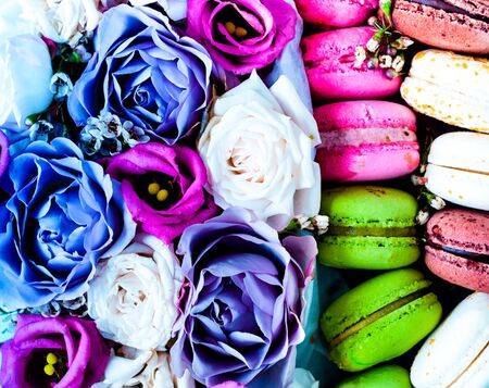 Food design in floral style. Interior decor or Festive concept from rosebuds in full bloom with colored macaroons. Close-up Stock Photo