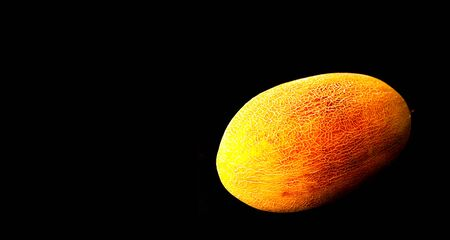 Whole fresh melon on black background. Organic food concept. Close-up, copy space