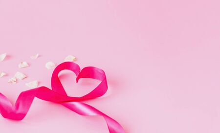 Festive pink ribbon in the shape of heart on pink background with white rose petals.  Template mock up of greeting card or text design. Close-up, copy space Stock Photo