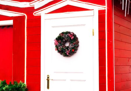 Christmas wreath on white door of red house. Festive background. Close-up, copy space