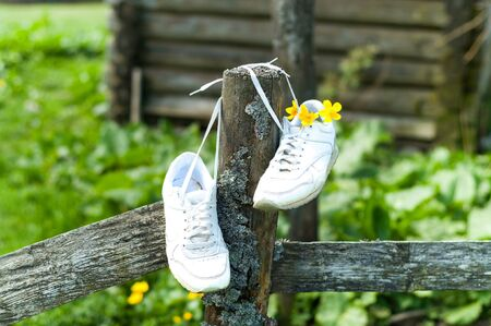 White Sneakers on authentic wooden fence, tied with laces. Summer equinox or Hello summer concept. Closeup, copy space.