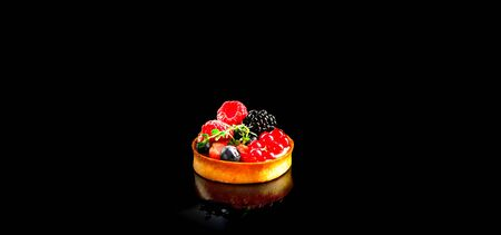 Cupcake or tiny pancake cereal with colorful berries on black background. Close-up