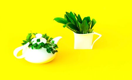 White ceramic teapot and cup with ecological plants on yellow background. The concept of healthy drink. Hello Summer. Close-up, creative copy space