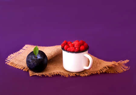 Fresh berries in a white vintage mug on burlap texture. Creative purple background with raspberries and plums. Close-up