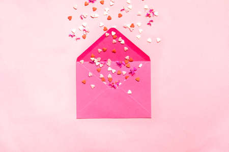 Abstract background with pink envelope and red hearts. Festive concept or Romantic Love message. Minimalist style, monochrome. Creative copy space Фото со стока