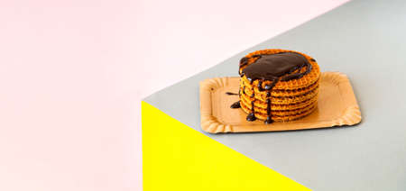 Traditional waffles with caramel and chocolate on geometric background. National Waffle Day. Trendy colors 2021. Creative copy space. Фото со стока