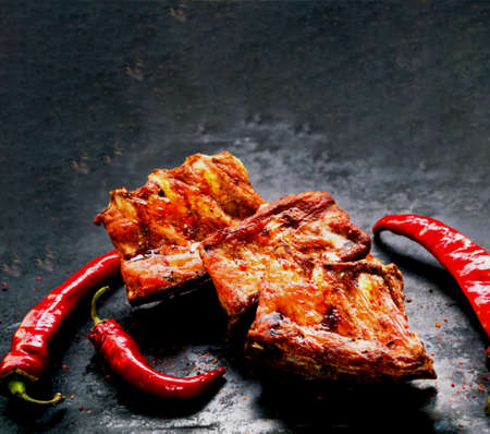 Spicy hot grilled spare ribs from BBQ served with hot chili pepper on vintage rusty metal background.Close-up