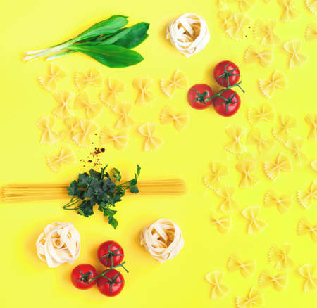 Uncooked pasta noodles with ingredients on yellow background. The concept of nutrition and sustainable health. Top view, copy space