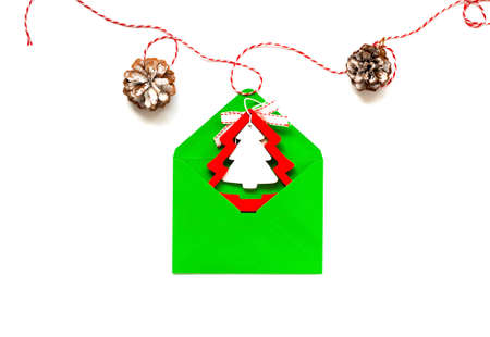 Green envelope with christmas wooden figurines on white background. Christmas design. Creative copy space for design and wrapping paper.
