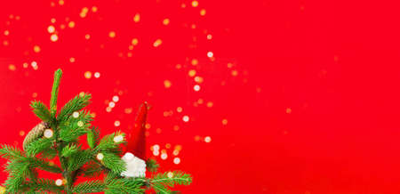 Fir branch with cones and Santa Claus on red background. Christmas decorations. Creative copy space. Close-up Фото со стока