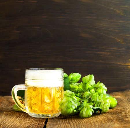 Fresh hops and glass mug with light beer on wooden background. International Beer Day or Oktoberfest beer festival. Close-up