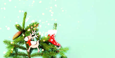 Fir branch with cones and and wooden toys on green background. Christmas decorations. Creative copy space for design. Close-up