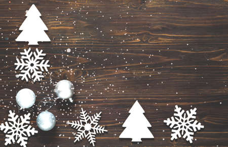 Decorative wooden snowflakes and silver balls on wooden background. Homemade gifts or Christmas and New Years decor. Close-up, creative copy space Фото со стока