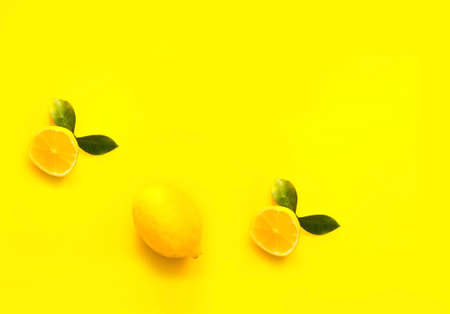 Whole and half lemon on yellow background. Color of the year 2021. Creative copy space, close-up Фото со стока