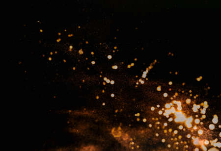 Abstract dark background with gold sparkles. Festive background for design. Blurred effect. Creative copy space. Close-up Фото со стока