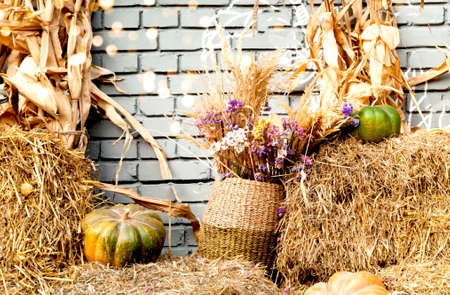 Straw and wildflowers in a wicker basket on a brick wall background. Autumn or summer mood. Close-up, creative copy space