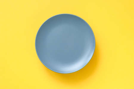 Gray plate for food on yellow background. Trending colors of 2021. Creative copy space