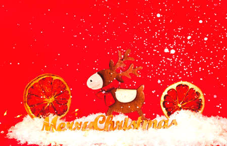 Wooden Christmas deer on red background. Christmas greeting card with place for your text.