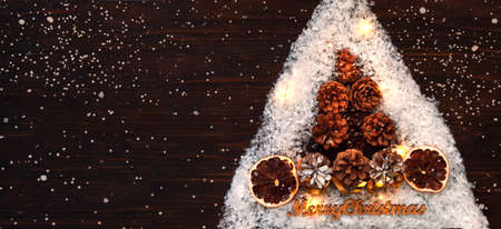 Christmas tree made of pine cones on a wooden background. Eco christmas holiday concept or new year greeting card with place for your text.