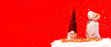 Christmas toy Santa Claus and a bag with gifts on a red background.Christmas greeting card. Creative copy space. Фото со стока