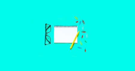 School stationery and white notebook on green background. The concept of Teachers day. Copy space