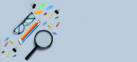 School stationery and magnifying glass on gray background. The concept of Teachers day. Copy space