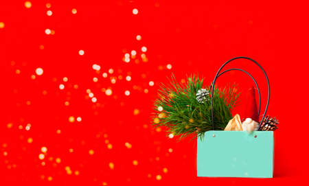 Gift bag with Christmas toys and pine branch on red background. Creative copy space