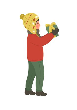 Christmas, New Year gift. Boy in winter warm clothing holding present on white background.