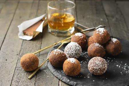 Chocolate rum truffles. Sweet dessert on a dark wooden background.