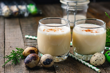 Traditional Christmas drink eggnog in a glass on a wooden background.