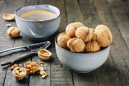 Walnuts in a blue bowl on a wooden table, nutcracker. Banque d'images