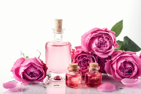 Roses, pink perfume essence in a bottle. Aromatherapy, spa treatments. Archivio Fotografico