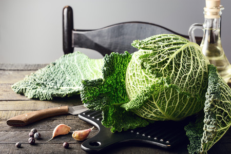 Fresh savoy cabbage on wooden table.