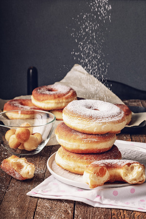 Donuts sprinkled with powdered sugar on a wooden table, delicious breakfast.
