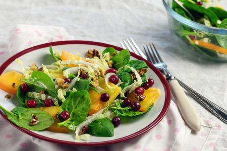 Frisse salade met spinazie, kaki, veenbessen en walnoten.