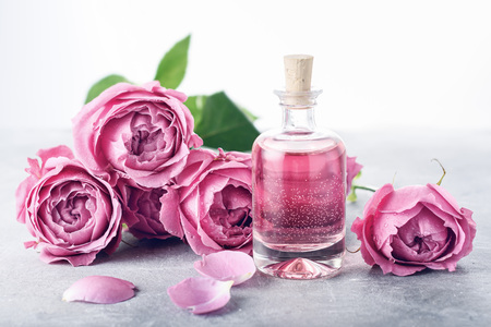 Perfumed Rose Water in glass bottle, roses. Banque d'images