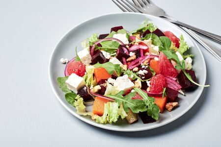 Vegetable salad with beets, pumpkin, grapefruit, cheese, arugula, onions and walnuts.