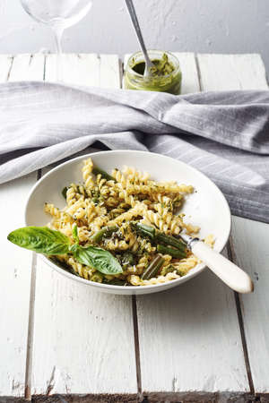 Fusilli pasta with green beans, pesto and basil on a white wooden table.