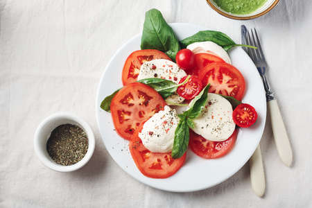 Caprese salad. Tomatoes, mozzarella cheese, basil leaves and pesto sauce.