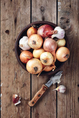 Yellow, red onions and garlic in a bowl on a wooden background.